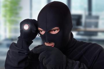 Mann mit Maske und Taschenlampe - Einbrecher