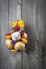 Braided bunch with onions, garlic and flowers, on wooden backgro