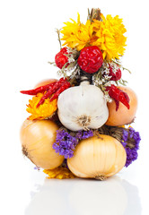 Braided bunch with onions, garlic and flowers, over white backgr
