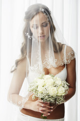 Pensive young bride in veil holding bouquet.