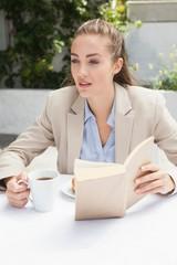 Beautiful businesswoman having a coffee reading book