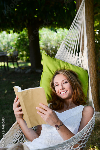 cheerful young woman reading a book in a hammock - 70380695