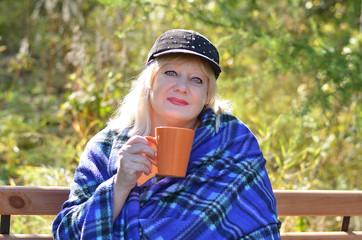 Женщина на скамейке пьёт чай.