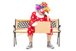 Sad clown sitting on bench and holding a sign