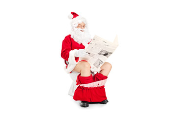 Santa Claus reading a newspaper seated on toilet