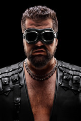 Dark portrait of a male biker with goggles