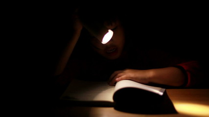 HD Dolly: Asian girl reading book in darkness, with flashlig