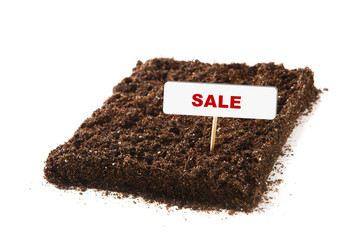 piece of soil with sale title, isolated on white