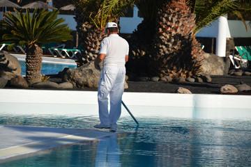 hombre limpiando una piscina