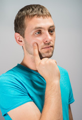 Portrait of a young businessman holding his chin with his hand.