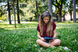 Portrait of young woman listening to music outdoors in a park.
