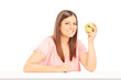 Young woman holding an apple and sitting at table