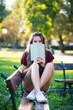 Young woman with book sit on a bench in the park. Filtered image