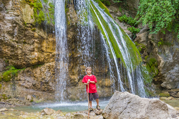 young happy smiling child boy on waterfall background