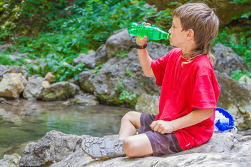 young happy smiling child boydrinking water on forest river back