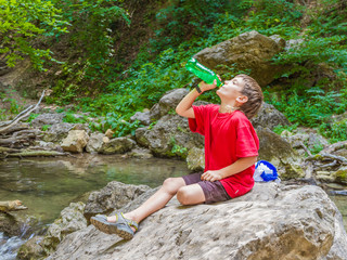 young happy smiling child boy drinking water on forest river bac