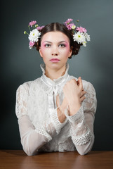 Young beautiful woman in white blouse and flowers