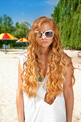 Young beatiful woman in sunglasses at the beach