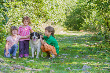 three kids - boy and girl - with dog outdoors