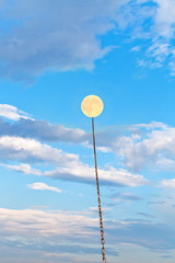 full moon tied on chain soars into blue sky