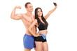 Attractive couple in sportswear taking a selfie