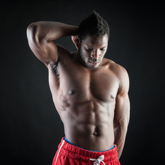 Strong young black man shirtless portrait against black backgrou
