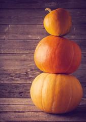 three pumpkins on wooden background