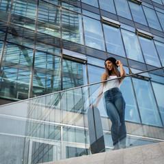 Teenager with skateboard full body portrait against modern build