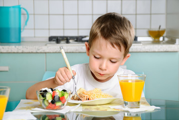 boy eating at the table, looking at the plate horizontal