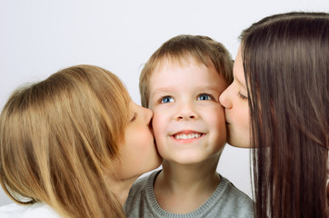 two girls kissing little cheerful boy