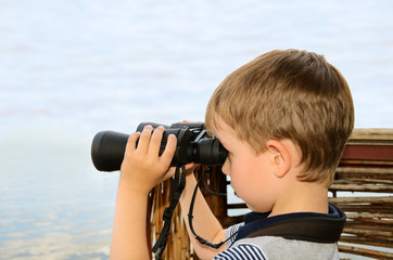 little boy looking through binoculars at sea. side view