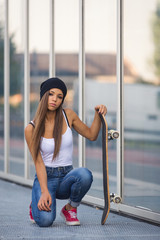Teenager with skateboard full body portrait outdoors.