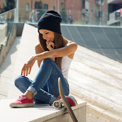 Teenager with skateboard portrait outdoors.
