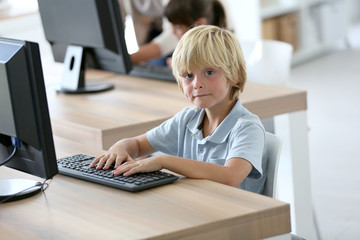 Portrait of school boy sitting in front of computer