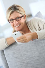 Blond woman reading text message on smartphone