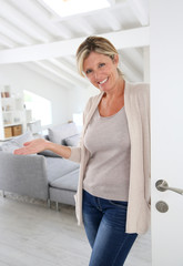 Mature woman welcoming people to come inside her home