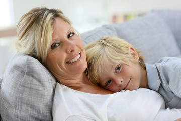 Portrait of happy mom and son relaxing on couch