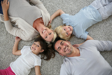 Upper view of family of four laid on carpet