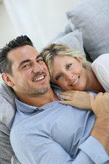 Mature couple relaxing in sofa at home