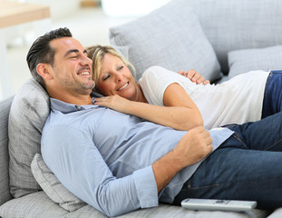 Middle-aged couple in sofa watching tv