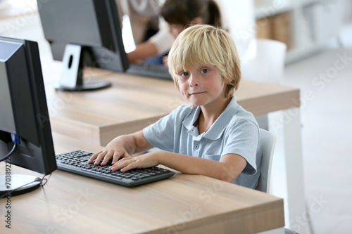 canvas print picture Portrait of school boy sitting in front of computer