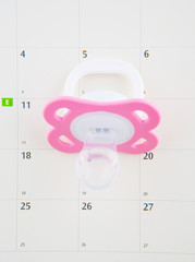Pregnancy concept delivery due date with calendar and pacifier