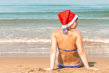 young girl in a Christmas hat on the sand