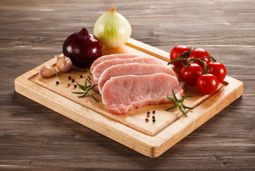 Raw pork chops on cutting board and vegetables