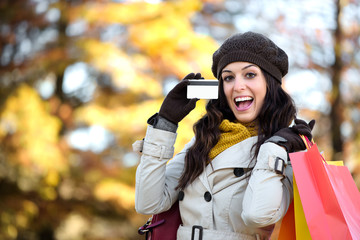 Woman with credit card and shopping bags in autumn