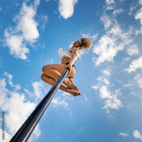 canvas print picture Attractive sexy woman pole dancer performing outdoors against bl