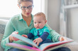 Cute baby reading with his mother
