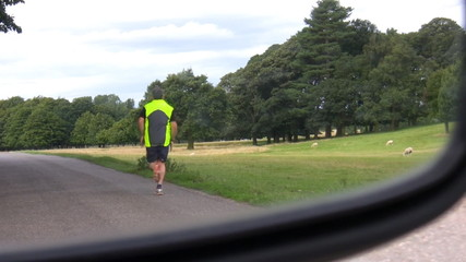 Man jogging, car mirror view
