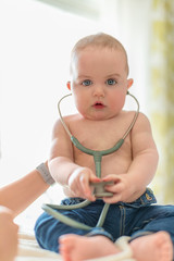 Cute baby listening to a stethoscope