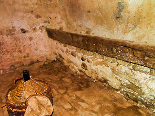 Old cellar with wine demijohn and manger. Filtered image.